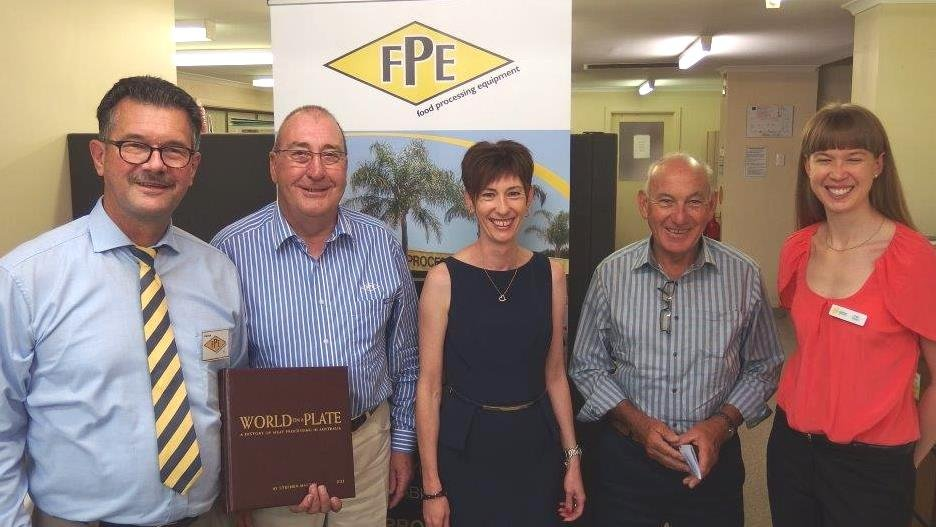 AMIC processor director Steve Martyn, left, presents copy number one of World on a Plate to TFI's Brian James, second from right, pictured with the Cancer Council's Kate Tonkin and FPE's Brian Carey and Jodie Teurlings.